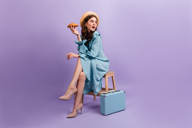 full-length-shot-young-lady-elegant-blue-dress-woman-sits-stool-suitcase-holds-delicious-croissant_197531-14322 (1)