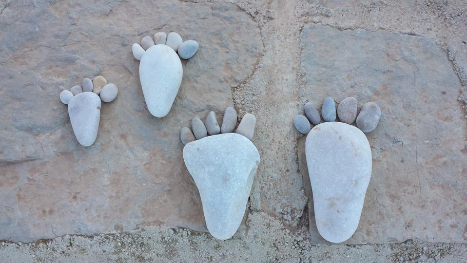 Chodidlá vyskladané z kamienkov položené na zemi