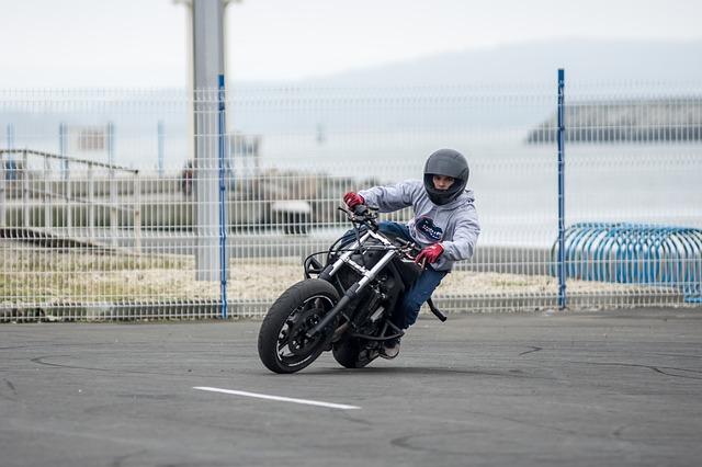 Chlapec v sivej bunde a modrých nohaviciach riadi motorku a má na hlave prilbu.jpg