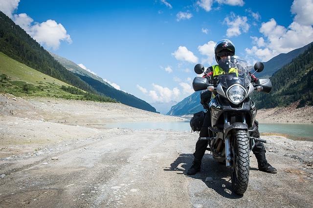 Muž v čiernej kombinéze s čiernou helmou sedí na motorke uprostred krásnej prírody.jpg