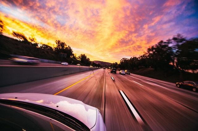 Auto ide po diaľnici počas západu slnka