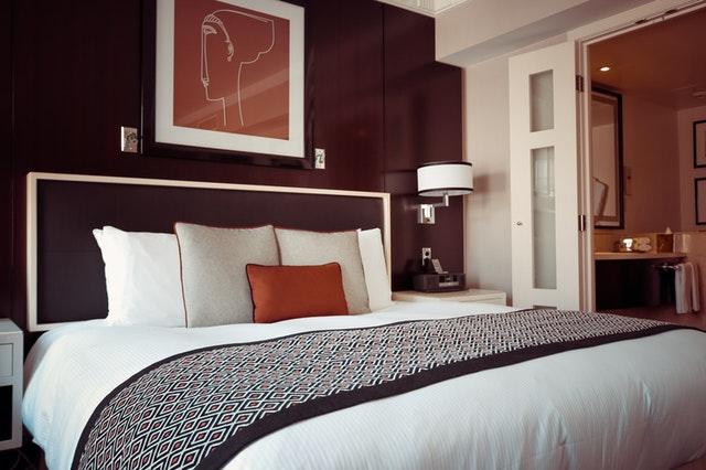 Široká posteľ s bielou prikrývkou