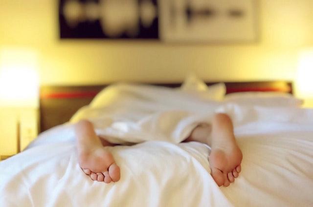 Človek s odkrytými nohami leží na posteli zakrytý dekou