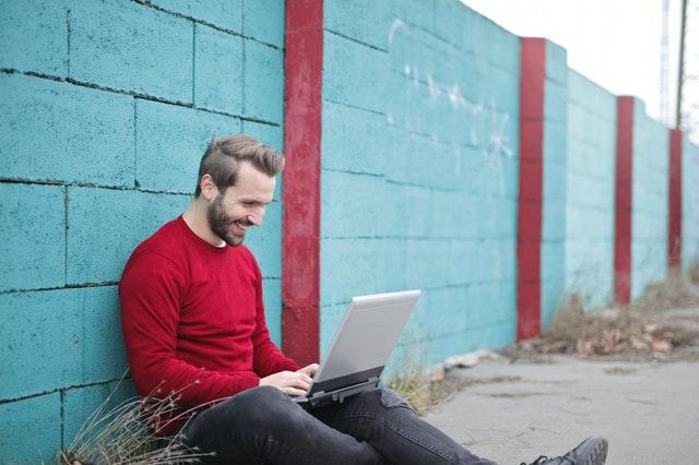 Muž v červenom svetri sedí pri tyrkysovom múre píše na notebooku